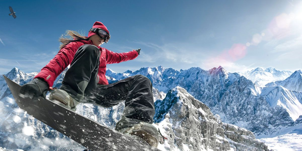 Close up image of female snowboarder making jump in snowy mountains